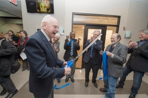 Professor Emeritus Harold Baldwin jokes with the audience after cutting the ribbon on the new site of the photo gallery that bears his name. Baldwin Photographic Gallery curator Tom Jimison is at center right holding the ribbon. Also celebrating are from left, behind Baldwin: Roy Moore, former dean of the College of Mass Communication; MTSU President Sidney A. McPhee; current Mass Comm Dean Ken Paulson; and Billy Pittard, chair of the Department of Electronic Media Communication.