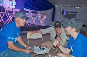 Ken Paulson (left), Mass Comm dean, confers with adjunct professor Pat Embry (center) and Michael Fleming, associate professor in Recording Industry, at the media tent on the grounds of the Bonnaroo Music and Arts festival. (MTSU photo)