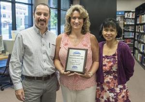 Yvonne Elliott, center, celebrates her award in the offices of the Center for Popular Music inside the Bragg Mass Communication Building. Dr. Greg Reish, the new director of the Center for Popular Music, and Dr. Zeny Panol, Mass Comm associate dean, celebrate with her.