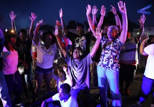 """""""Don't shoot us,"""" cry protestors as they confront police officers arriving to break up a crowd on Canfield Dr. in Ferguson on Saturday, Aug. 9, 2014.  Earlier in the day police had shot and killed an 18-year-old man on the street. Photo by David Carson."""