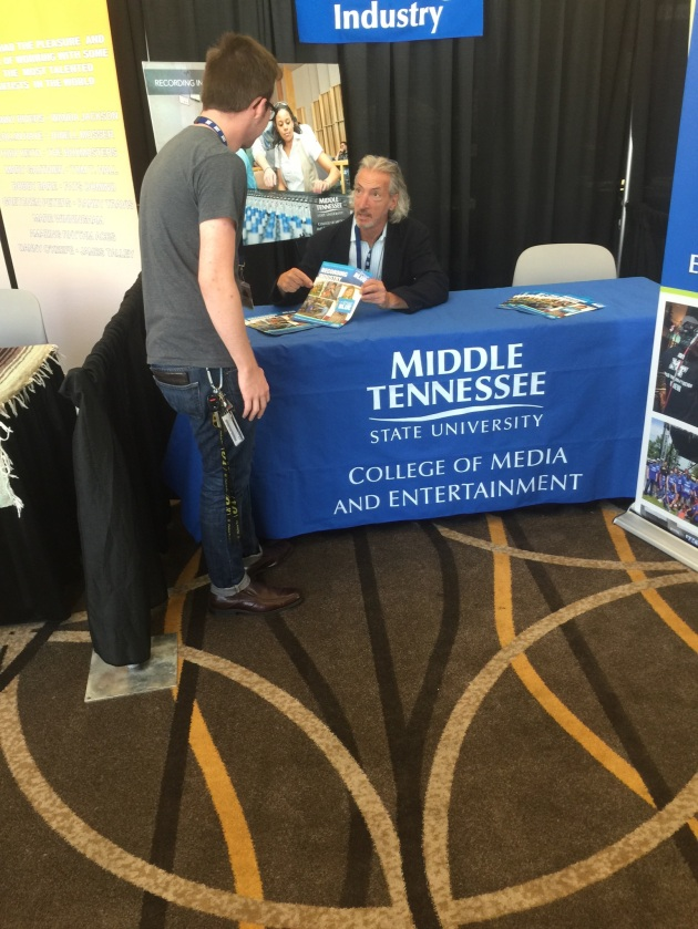 Matthew O'Brien, associate professor in the Department of Recording Industry, helps a passerby at MTSU's College of Media and Entertainment informational booth at the 16th annual Americana Music Festival and Conference at the Hutton Hotel and throughout downtown Nashville.