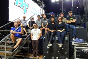 Mike Forbes, seated at front left, assistant director of technologies for MTSU's College of Media and Entertainment, is joined by his Video Technology class students on stage in Murphy Center early Oct. 1 in front of the customized 30-foot-by-20-foot video wall they created for the Homecoming 2015 concert featuring Icona Pop. Shown on the front row with Forbes are senior electronic media communication majors Paul Douglas, Angie Carter and Adrienne Kelley. Seated on the stairs and in the second row are, from left, junior EMC majors Zack Johnson, Barrett Depies and Sara Daily; senior EMC majors David Marrow and Robbie Weaver; junior EMC major Sokoya Crockett; seniors Wes Jenkins and Trevor Ball and junior Alex Briley. (MTSU photo by News and Media Relations)