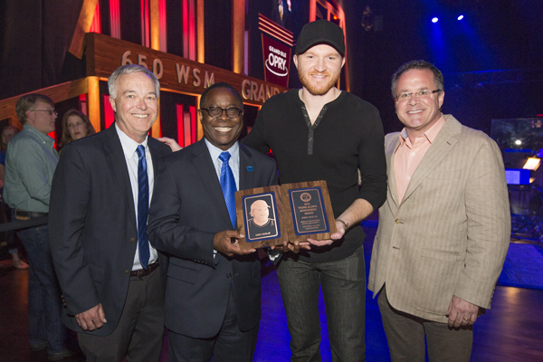 Recording Industry alumnus and country music star Eric Paslay, second from right, holds his 2015 MTSU Young Alumni Achievement Award, presented March 15 at his Grand Ole Opry performance. From left are Ken Paulson, dean of the College of Media and Entertainment; MTSU President Sidney A. McPhee; Paslay; and MTSU alumnus Pete Fisher, general manager of the Opry. (Courtesy of Grand Ole Opry)